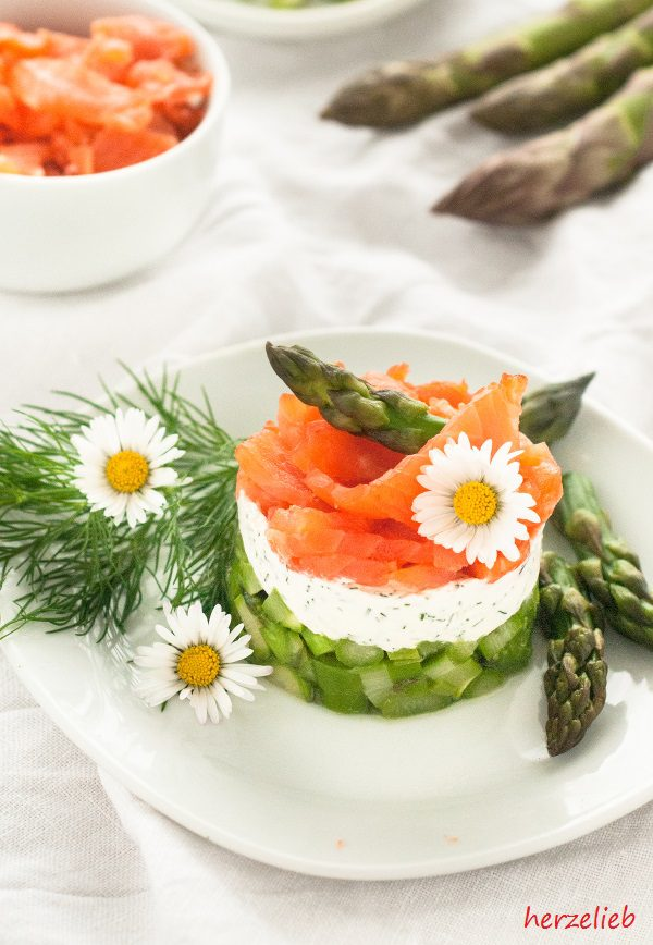 Spargel-Salat geschichtet auf einem Teller mit Spargel-Spitzen und Gänseblümchen