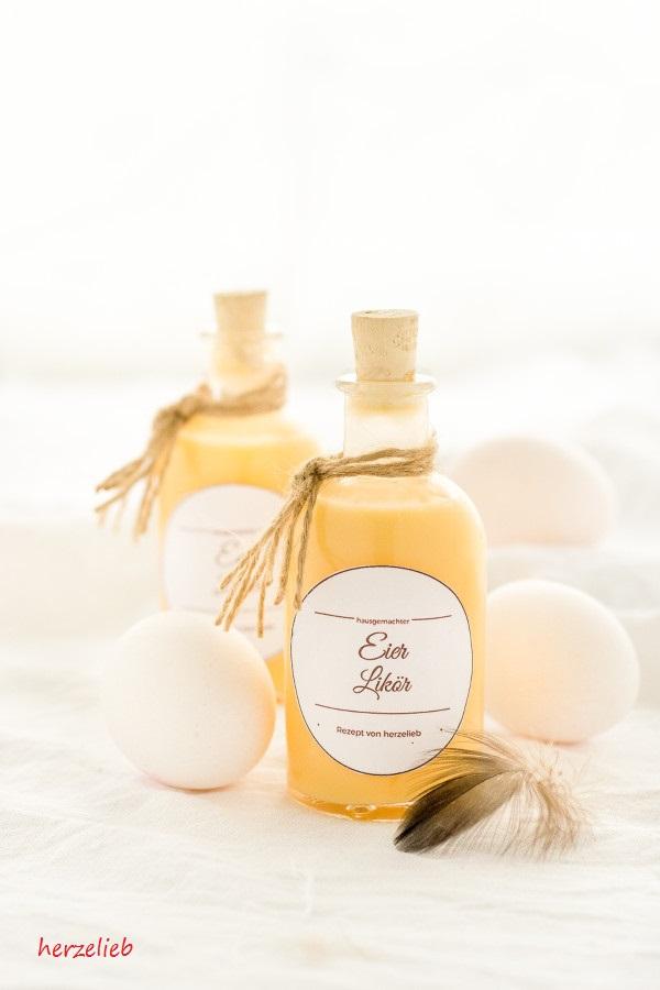 Zwei Flaschen selbstgemachter Eierlikör, Eier, Feder