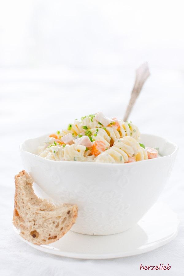 Klassischer Nudelsalat in weißer Schale mit Brot