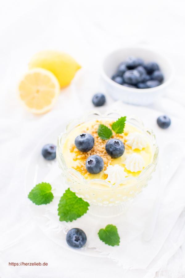 Dänische Citronfromage oder Zitronencreme im Glas mit Blaubeeren, Zitronenmelisse und Haselnusskrokant
