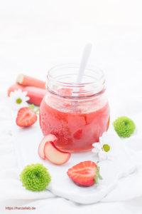 Rhabarbermarmelade im Glas mit einem Löffel, Früchten und Blumen