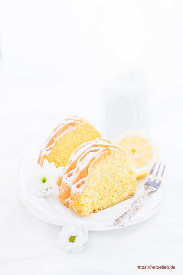 Grießkuchen in Scheiben auf einem Teller mit Zitronen und Blumen