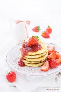 Grießbrei Pfannkuchen gestapelt mit Erdbeeren und Grütze
