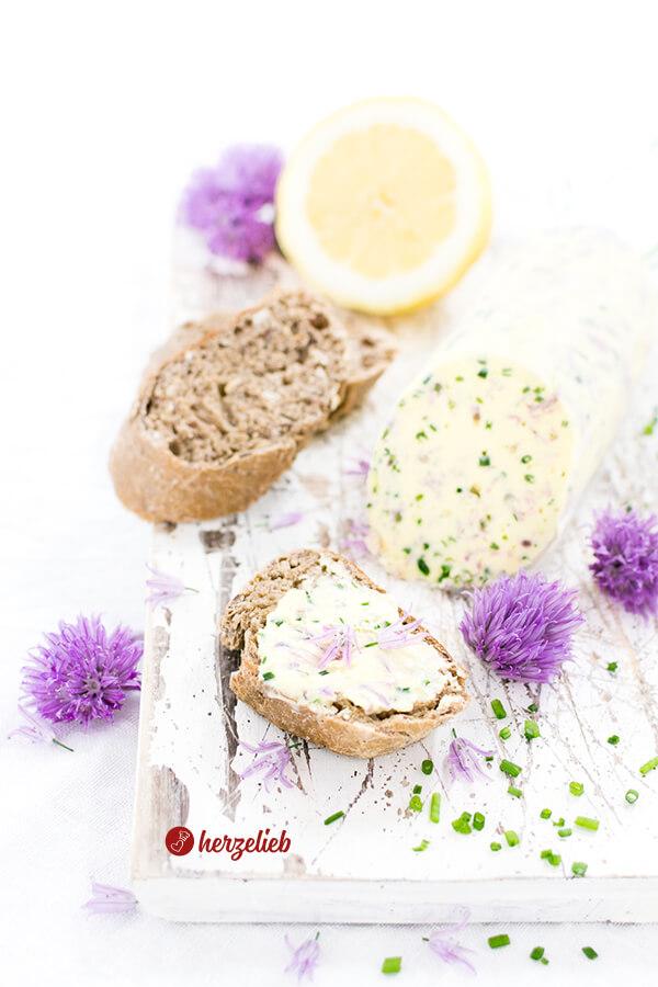 Schnittlauchblütenbutter auf Brot mit Blüten und eine Butterrolle