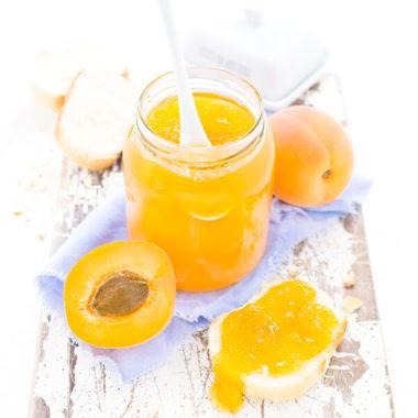 Perfekte Aprikosenmarmelade im Glas mit Marmeladenbrot