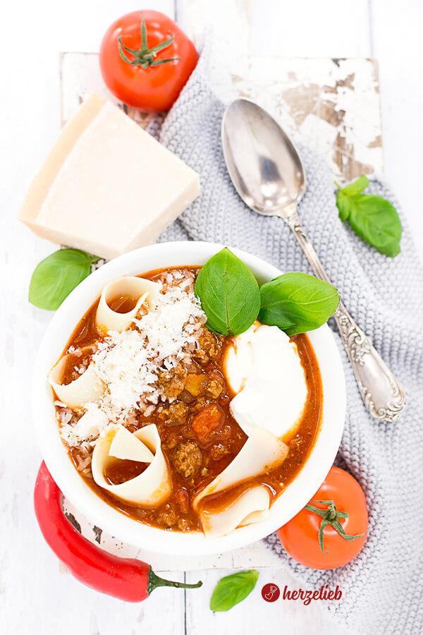 Lasagnesuppe in einer Schale mit Parmesan, Tomate, Chilie und Basilikum und Creme Fraiche