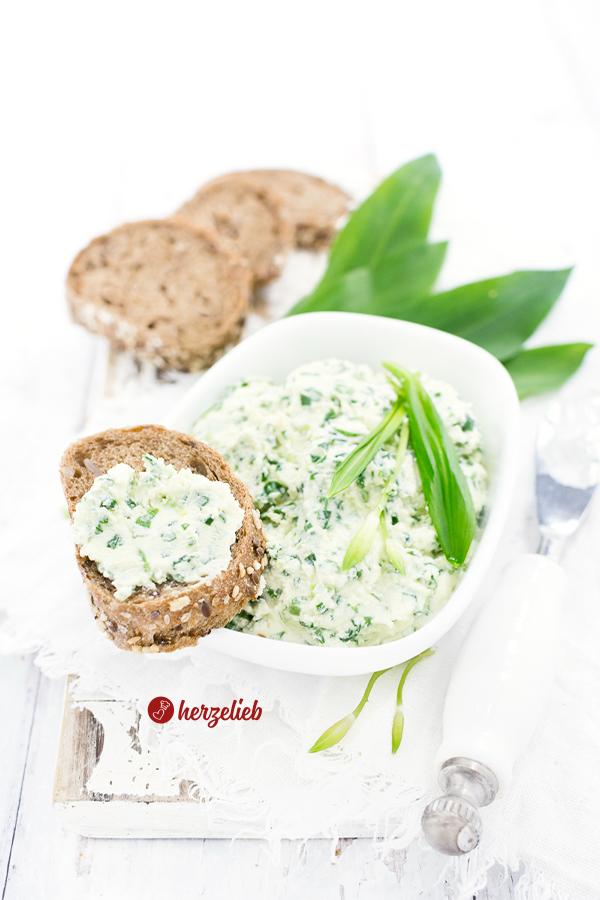 Bärlauchcreme in einer weißen Schale mit einem bestrichenen Brot auf dem Schalenrand