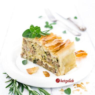 Ein Stück Hack-Zucchini-Lasagne mit Feta im Filoteig nach einem Rezept von herzelieb. Dekoriert mit Oregano und Rosmarin