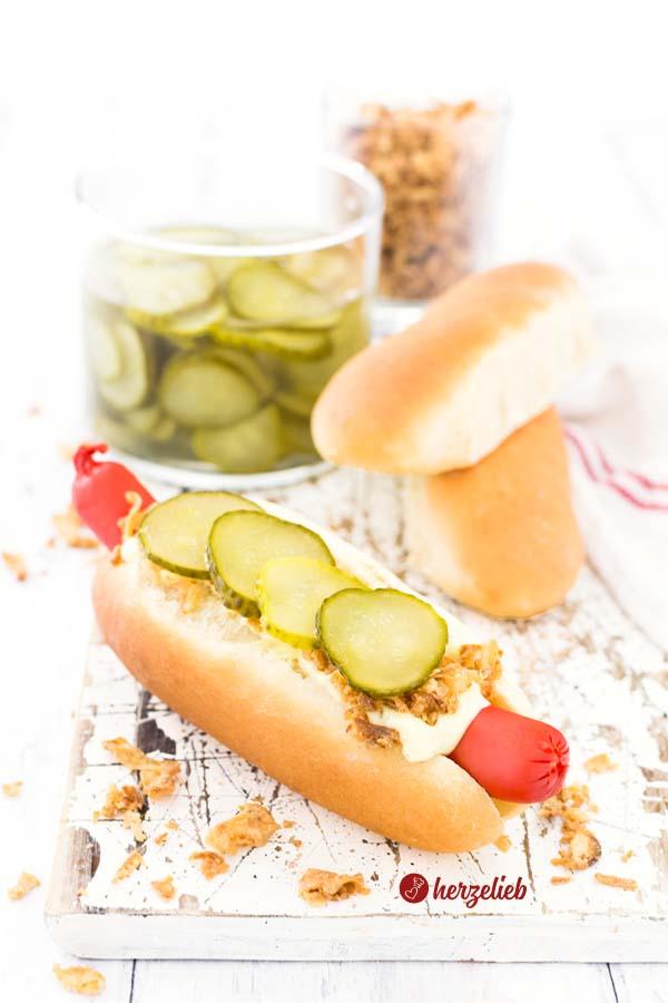 Hot Dog Brötchen selber machen. fertiges Hot Dog und zwei selbstgebackene Hot Dog Brötchen. Mit Agurker und Röstzwiebeln