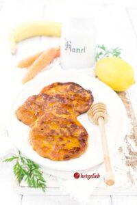 Saftige Karottenkuchen Pfannkuchen auf einem Teller mit einem Honiglöffel, Karotten, zitronen, Banananen vom Foodblog herzelieb