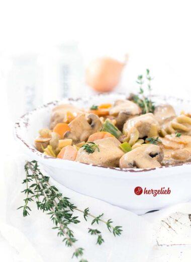 Filet-Schlemmertopf in einer weißen Schüssel mit braunem Rand. Mit Karotten, Champignons und Schweinefilet