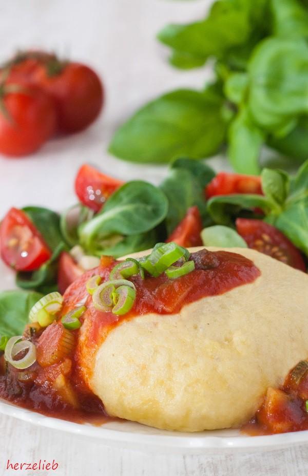 Rezept für herzhaft gefüllte Germknödel mit Tomatensoße.