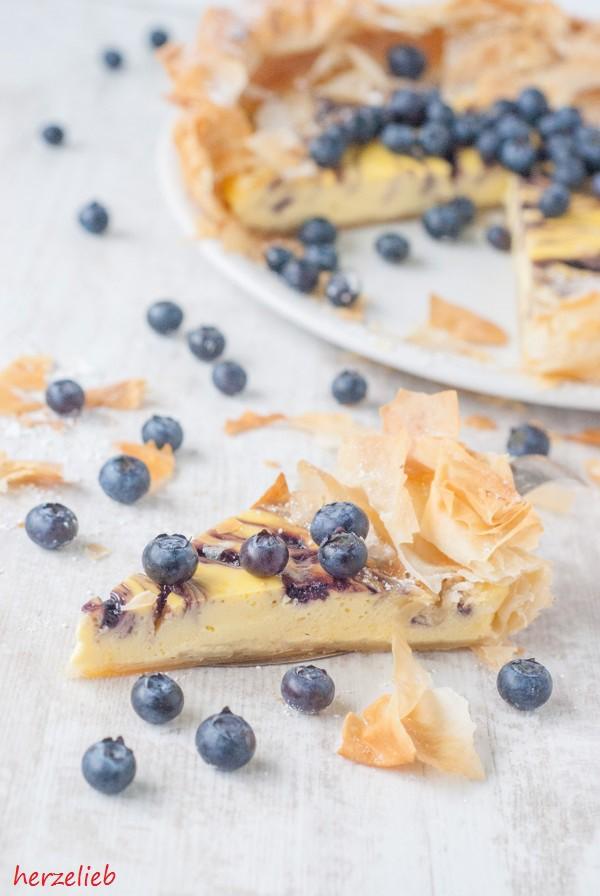 Angeschnittener Käsekuchen mit Blaubeeren im Filoteig