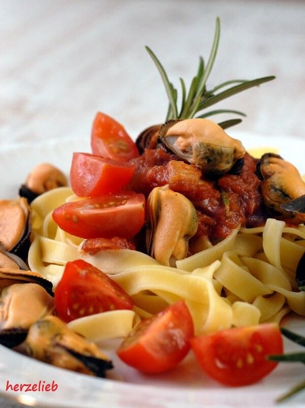 Miesmuscheln auf dem Teller angerichtet - mit Tomatensoße, Tomaten und Nudeln