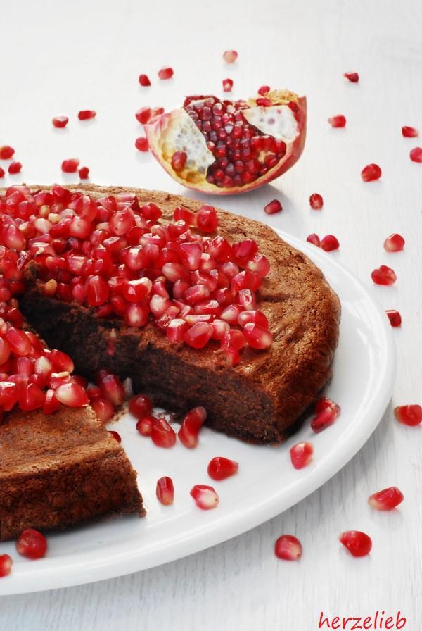 Angeschnittener Schokoladenkuchen mit Granatapfelkernen. Der Kuchen ist von innen cremig und muss gut gekühlt serviert werden!